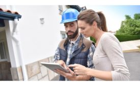 Man in blue hard hat looking at Ipad with woman