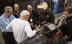 Educators gather round a Lincoln Electric pipe-welding engineer