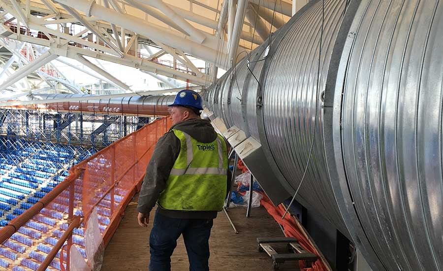 Triple S foreman Matthew Macauley walks on a platform past some of the large diameter ductwork installed at the Arthur Ashe Stadium.