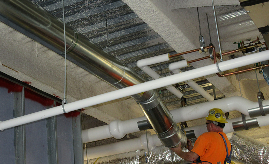 An installer hangs a section of pipe on the St. Elizabeth's Hospital project.